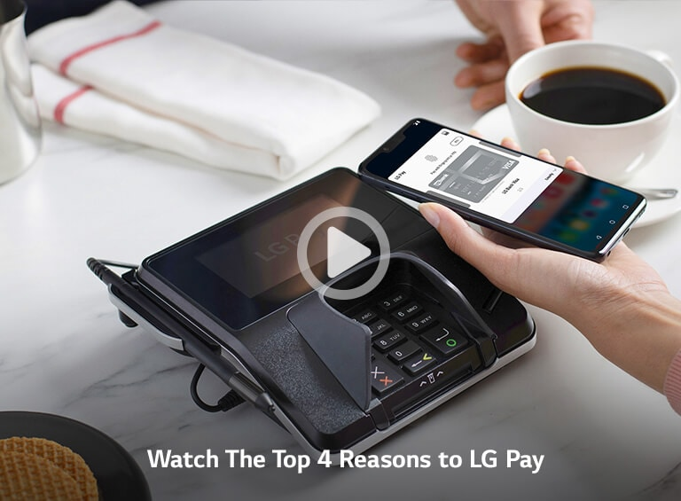 Hand holding an LG phone over payment machine at a restaurant.