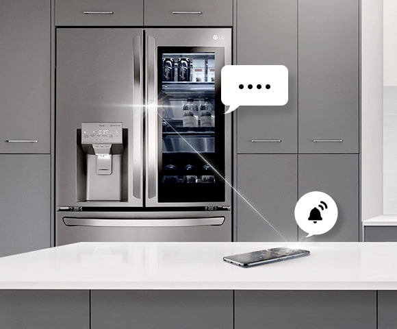 LG smart refrigerator and smarphone in the kitchen sends notification to user through speech bubble icon.