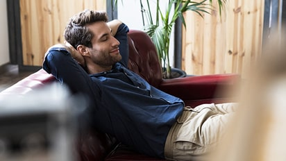 A man is satisfied with the service of LG ThinQ home appliance remote control and is resting comfortably on the couch.