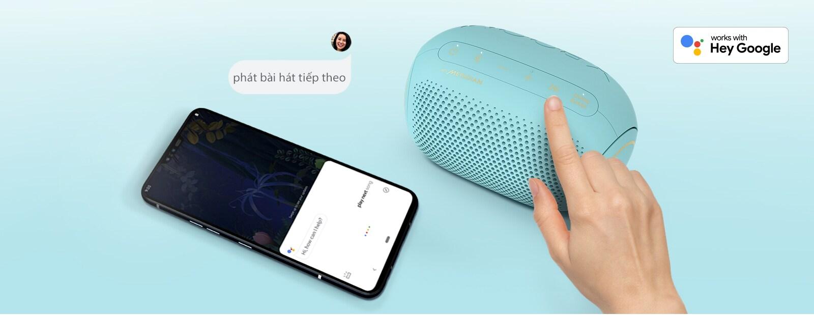 Hình chụp từ phía trên với một ngón tay đang ấn nút trên loa LG XBOOM Go PL2B và một chiếc điện thoại thông minh đặt cạnh có bong bóng thoại và logo Google