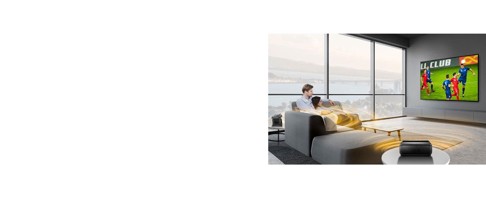 Một người đàn ông và phụ nữ đang xem trận đấu thể thao trên TV trong phòng khách với loa phía sau Bluetooth