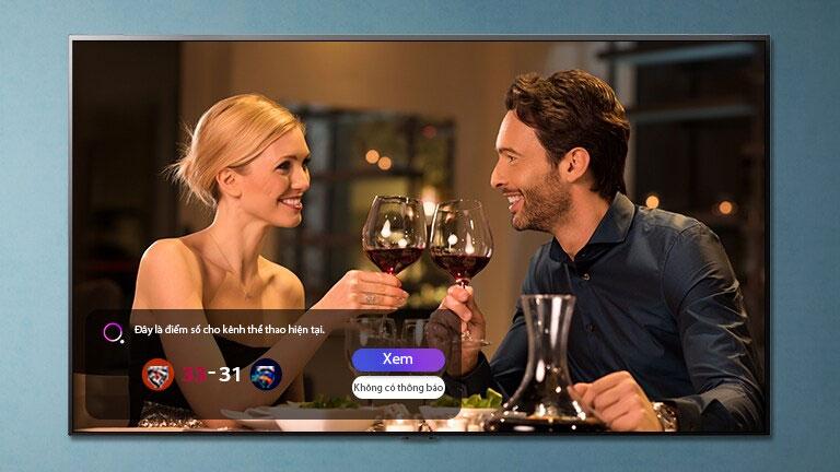 Một người đàn ông và một người phụ nữ đang cụng ly trên kính màn hình TV trong khi thông báo thể thao đang hiển thị