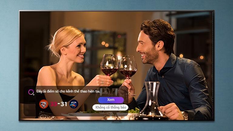 Một người đàn ông và một người phụ nữ gõ leng keng trên kính màn hình TV trong khi thông báo thể thao đang được thông báo