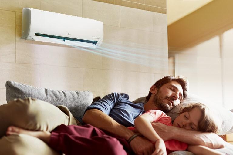 Người cha và con gái ngủ trên một chiếc ghế dài bên dưới máy điều hòa không khí đang thổi không khí ra bên trên.