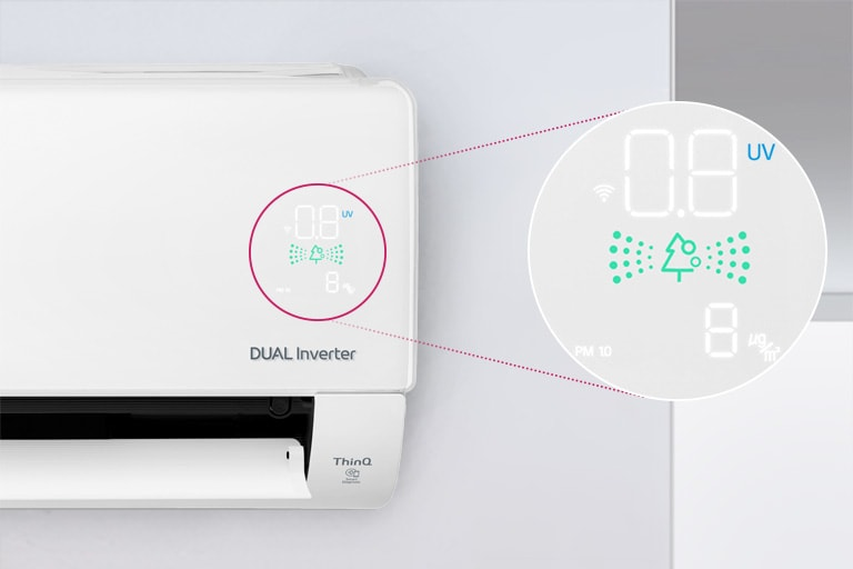 Một nửa máy điều hòa không khí LG có thể nhìn thấy được lắp trên tường với cửa trước mở cho biết máy đang bật. Một vòng tròn xung quanh đèn chất lượng không khí của máy và một vòng tròn phóng đại được mở ra để hiển thị các đèn màu xanh lá cây của bảng chất lượng không khí và các con số để hiển thị chất lượng không khí chính xác. Logo DUAL Inverter có thể nhìn thấy trên máy.