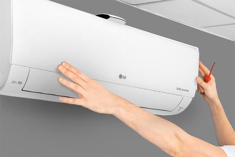 Hình ảnh mặt bên của máy điều hòa không khí có thể nhìn thấy trên tường. Hai bàn tay đang vươn lên, một tay cầm dụng cụ, cho thấy việc lắp đặt dễ đang.
