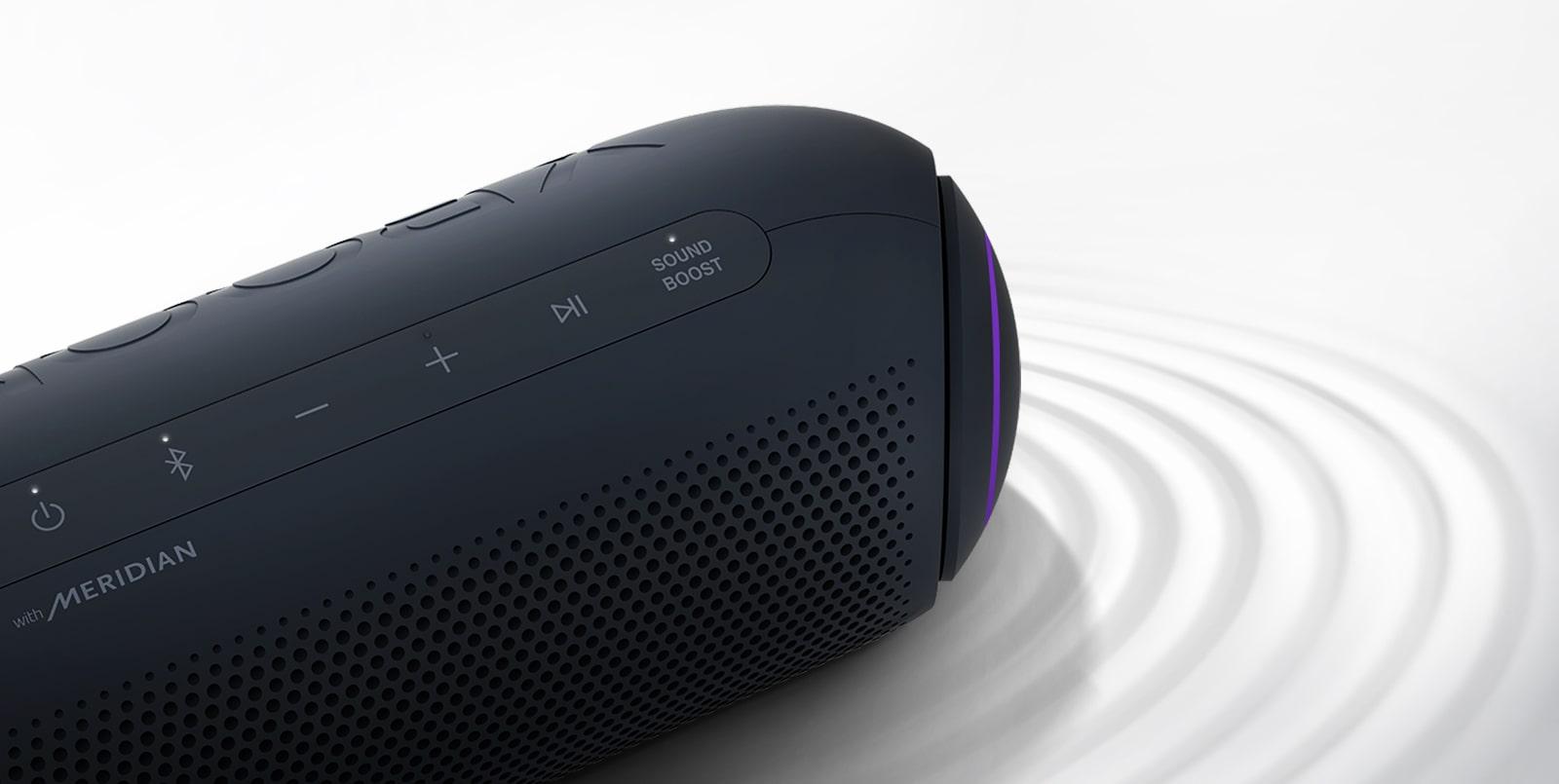 LG XBOOM Go hướng về góc trên bên phải đang bật đèn màu tím trên nền trắng, có hiệu ứng gợn sóng bên dưới sản phẩm.