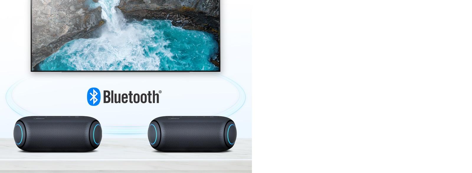 Trên bàn có hai chiếc LG XBOOM Go đèn xanh da trời đặt trước một chiếc TV đang phát hình thác nước.