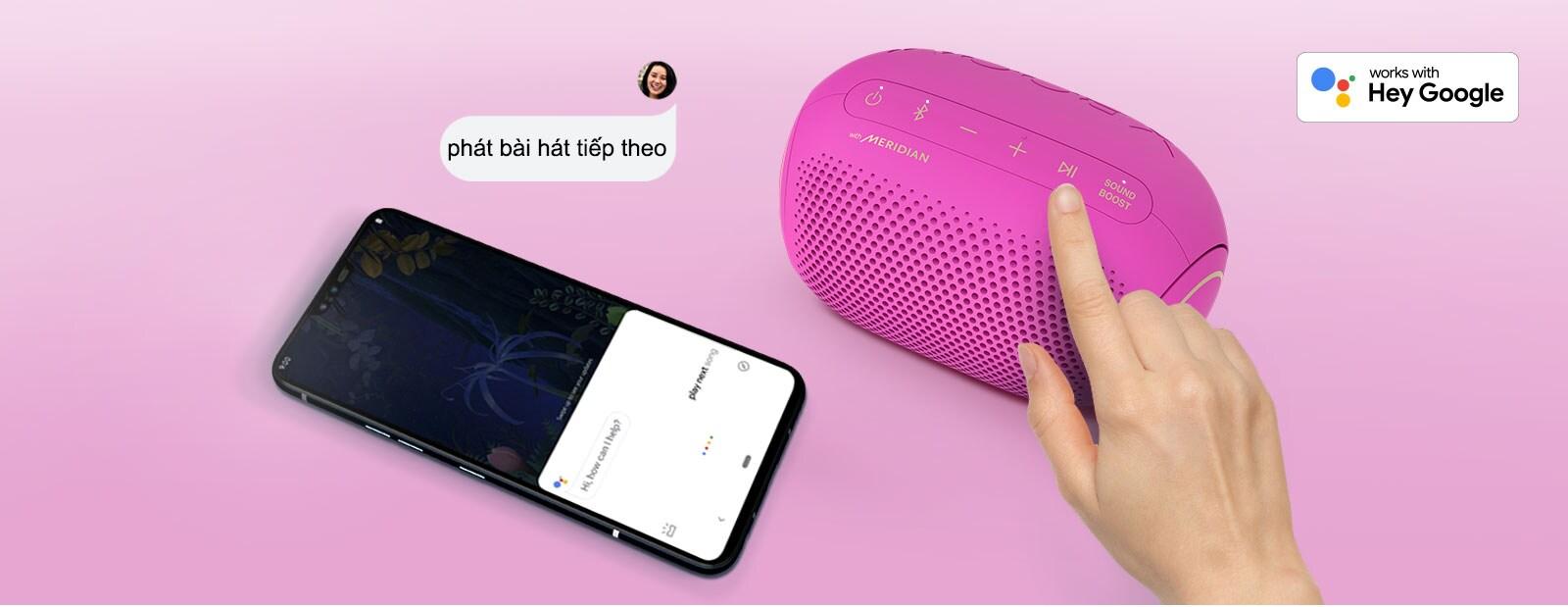 Hình chụp từ phía trên với một ngón tay đang ấn nút trên loa LG XBOOM Go PL2C và một chiếc điện thoại thông minh đặt cạnh có bong bóng thoại và logo Google