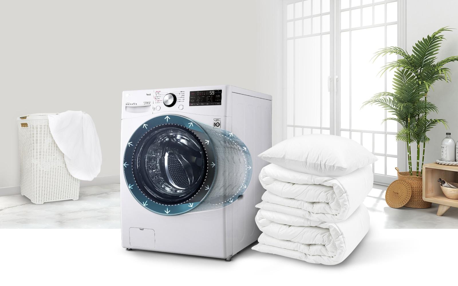 Một chiếc máy giặt nhìn nghiêng để có hình ảnh từ phía trước/bên cạnh với một chồng chăn và gối bên cạnh. Có thể nhìn xuyên thấu máy giặt nên sẽ thấy đường viền của lồng giặt với các mũi tên cho biết độ rộng.