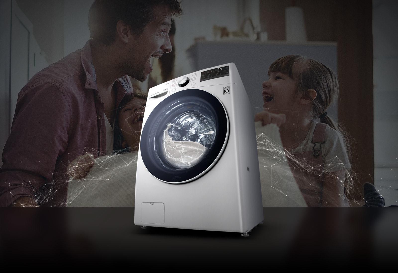 Bố và con gái đang cười ở phía sau trong lúc cầm một cái chăn sạch. Máy giặt cửa trước màu trắng ở phía trước.