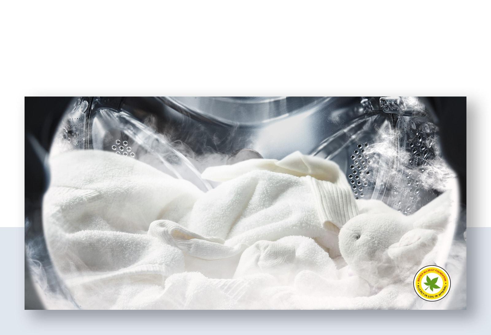 Hình ảnh một chiếc áo choàng trắng mềm mại và thú nhồi bông trong làn hơi nước trong lồng giặt của máy giặt.