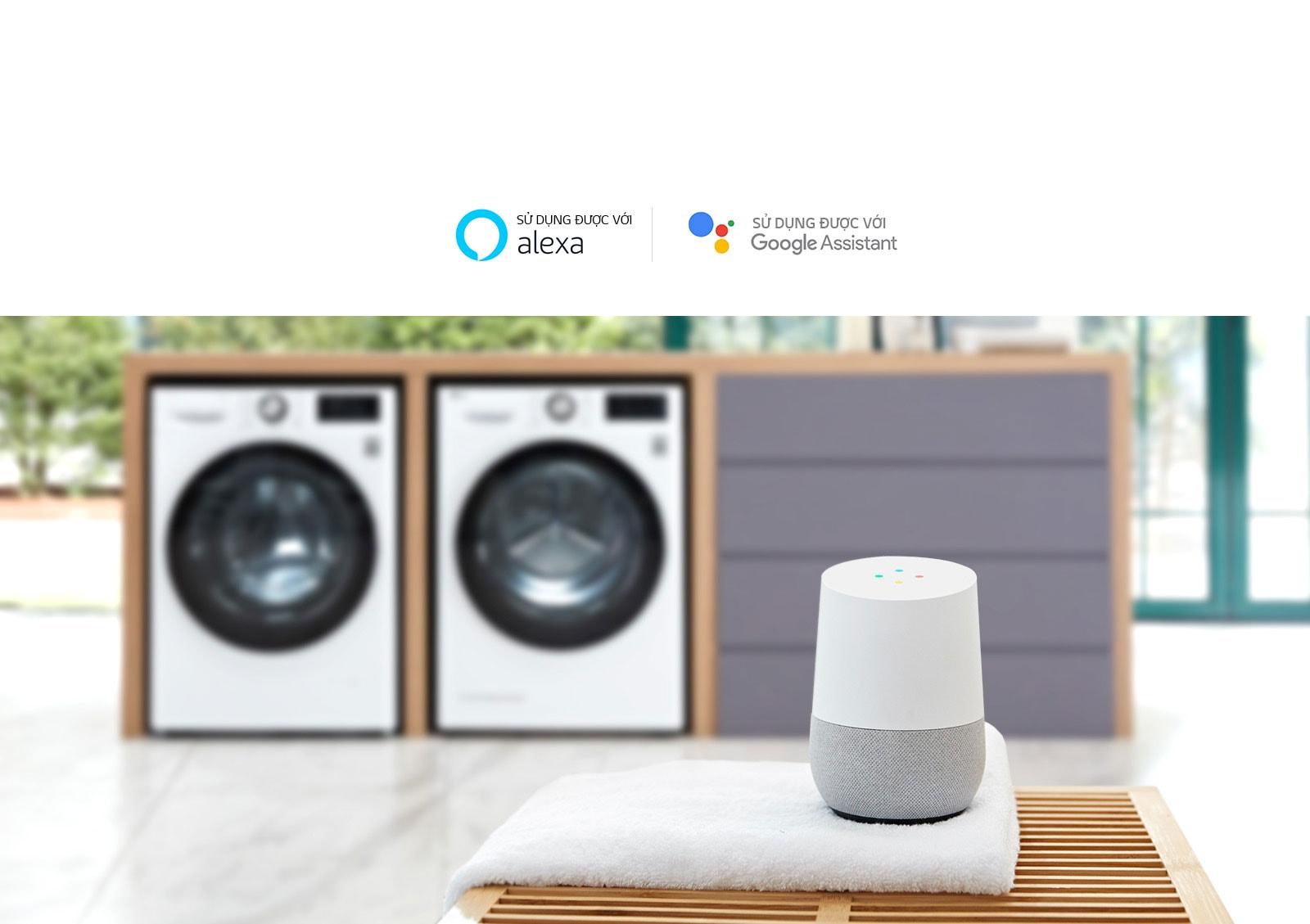 Hình ảnh phía sau là hai máy giặt cửa trước trong bàn gập quần áo tích hợp bị làm mờ, với LG ThinQ trên một chiếc khăn đặt trên bàn ở phía trước.