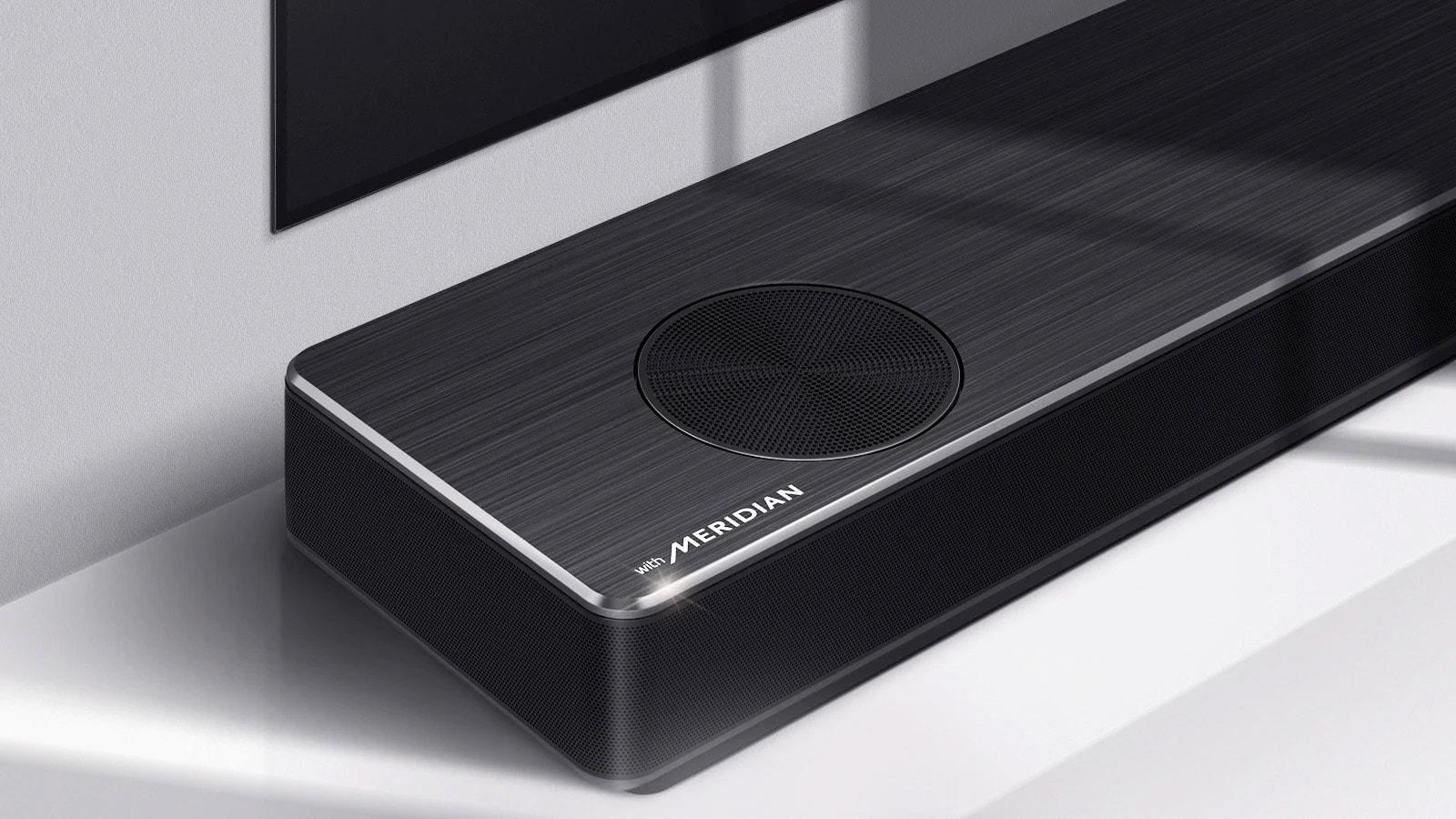 Cận cảnh mặt trái của LG Soundbar với logo Meridian được hiển thị ở góc dưới cùng bên trái trên sản phẩm. Hiển thị cả cạnh phía dưới bên trái của TV.