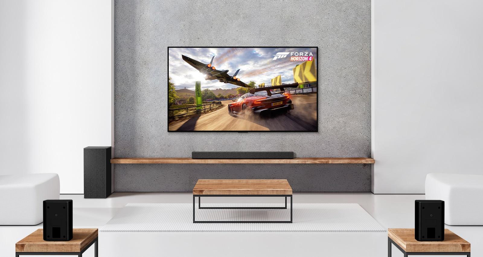 Loa siêu trầm, loa soundbar và TV trong phòng khách màu trắng. Xe đang chạy và tàu vũ trụ trên màn hình TV.