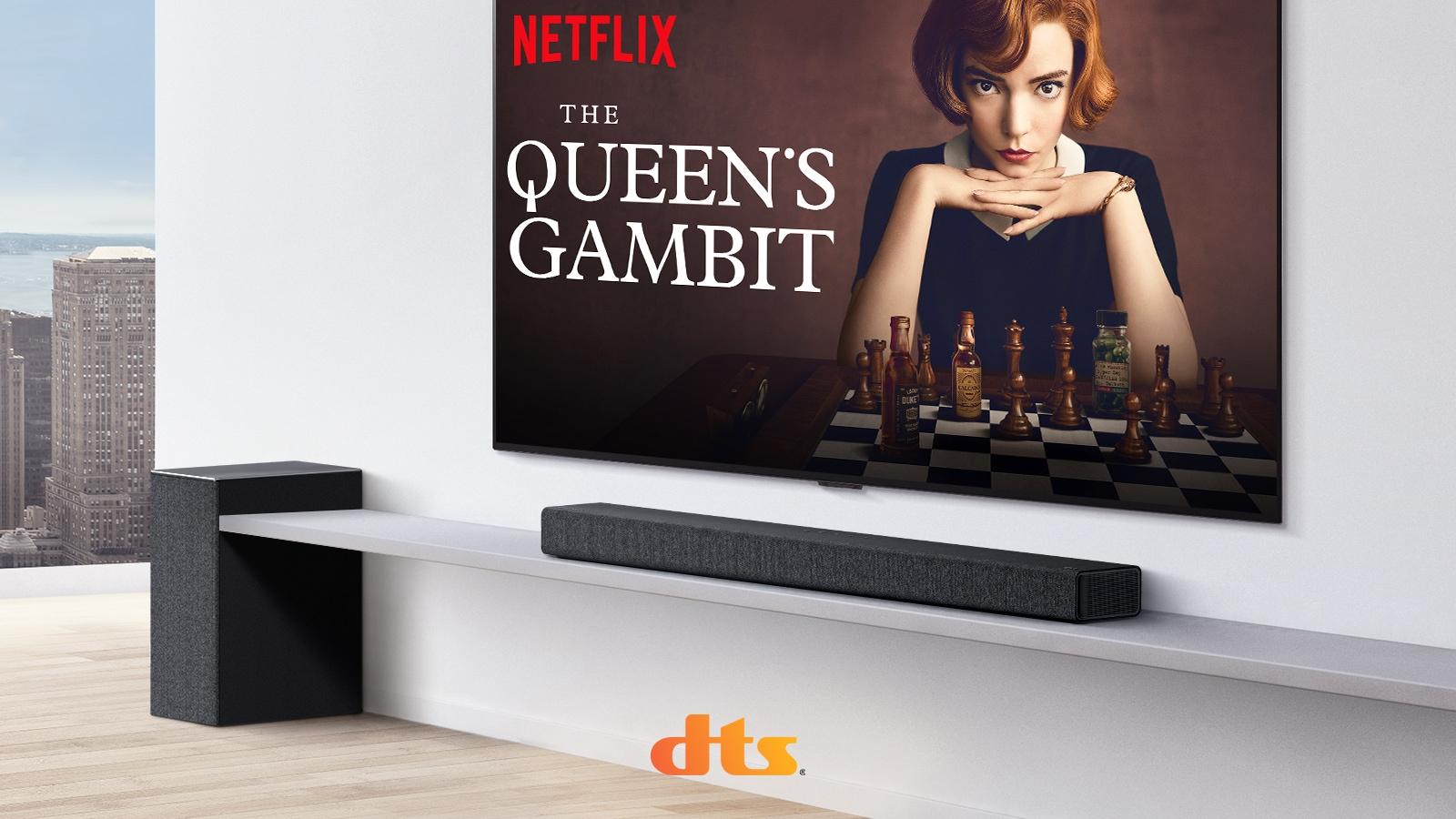TV treo trên tường. Áp phích của chương trình truyền hình trên màn hình TV. LG Soundbar nằm ngay bên dưới TV trên kệ màu trắng với loa siêu trầm ngay bên cạnh. Logo Dolby Atmos và DTS:X được hiển thị ở chính giữa bên dưới của hình ảnh.
