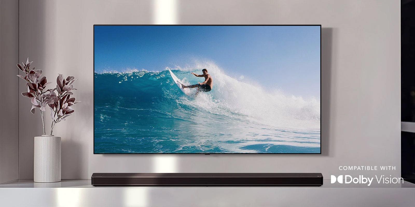 TV treo trên tường. Tv thể hiện một người đàn ông đang lướt trên con sóng lớn. LG Soundbar nằm ngay bên dưới TV trên kệ trắng. Một chiếc bình với một bông hoa ngay bên cạnh loa soundbar. (phát video)