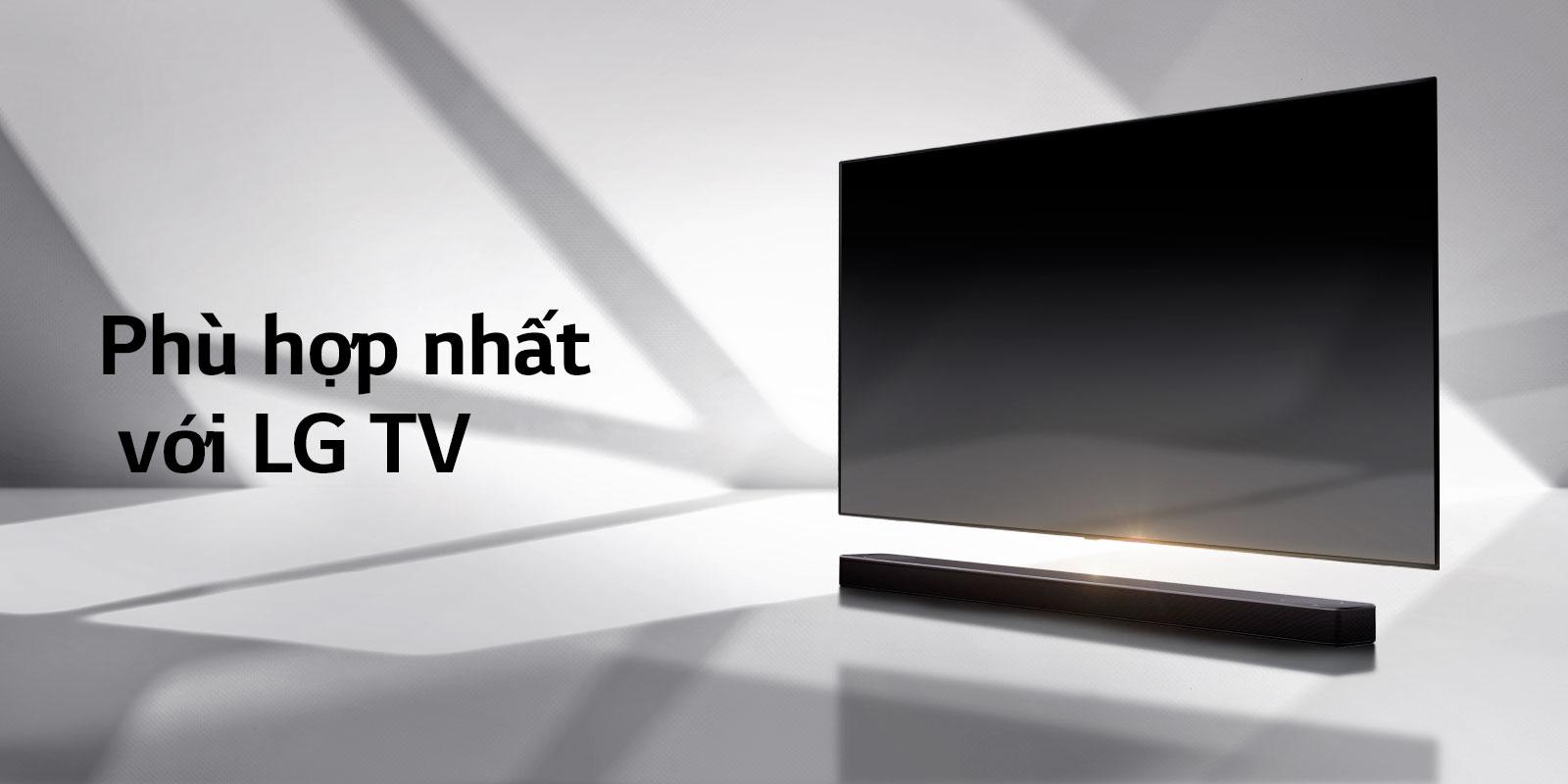 Loa soundbar và TV được đặt trên sàn màu trắng và có một cái bóng hiện ra từ bên ngoài ngay phía sau.