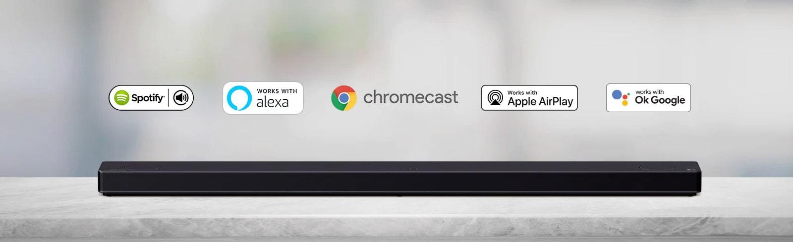 Loa soundbar đặt trên kệ màu xám và có logo nền tảng AI, theo thứ tự spotify, Alexa, Chromecast, Apple Airplay và OK Google từ trái sang phải.