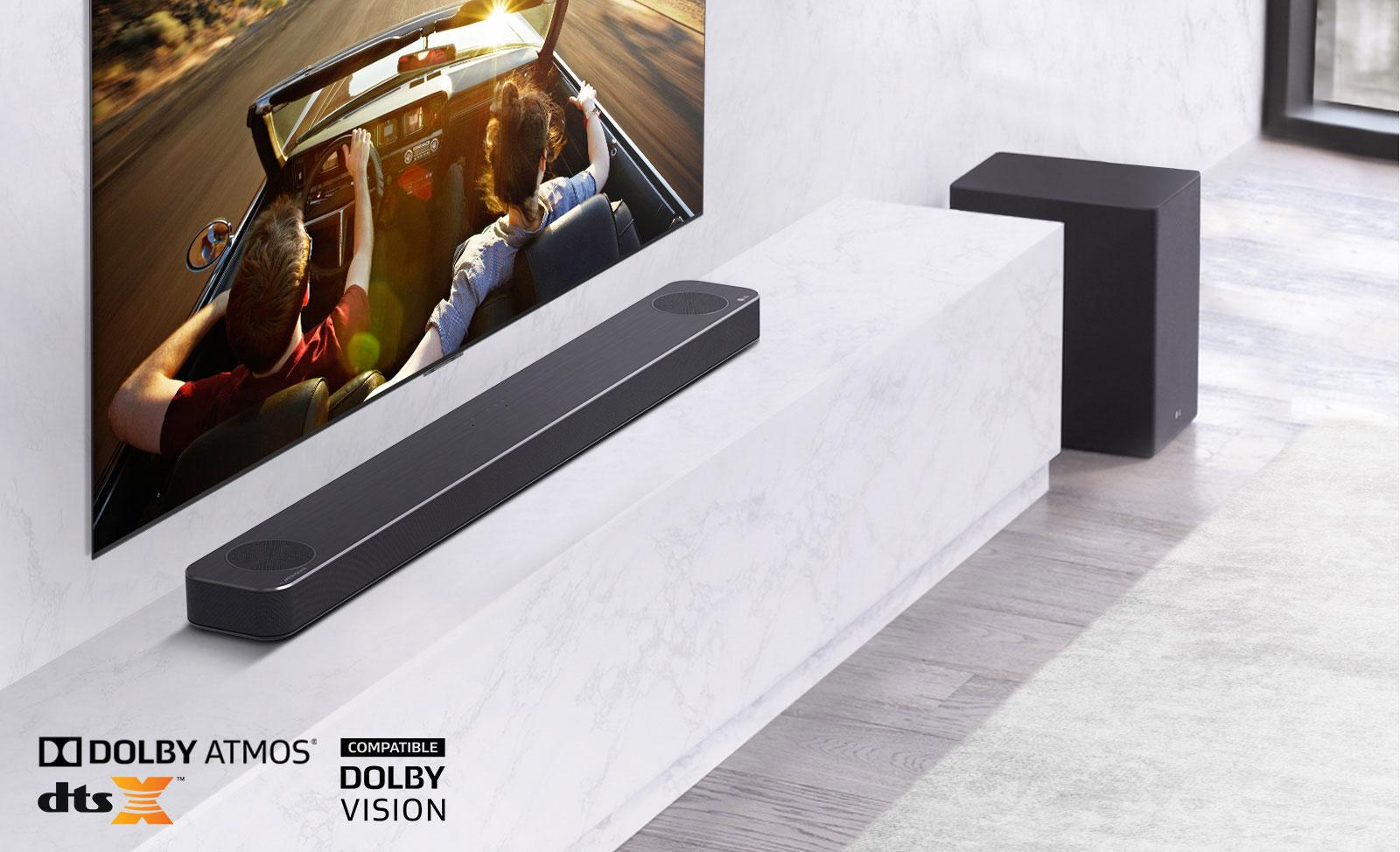 TV ở trên tường, loa thanh LG phía dưới, đặt trên kệ đá cẩm thạch trắng, có loa trầm ở bên phải. TV hiển thị một đôi nam nữ trong xe hơi.