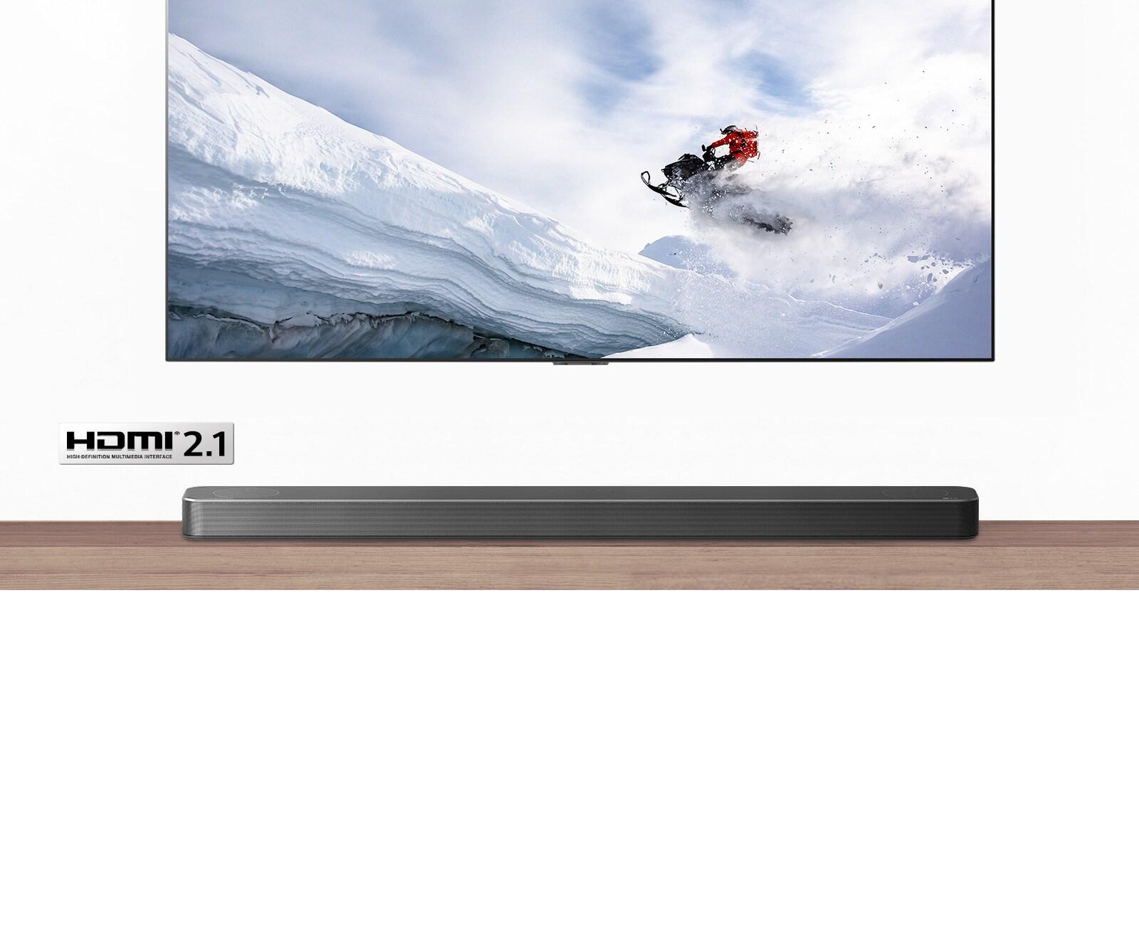 TV và Loa thanh nhìn từ phía trước. TV chiếu một người đang đi xe trượt tuyết trên vùng núi tuyết. Logo HDMI 2.1 bên dưới TV.