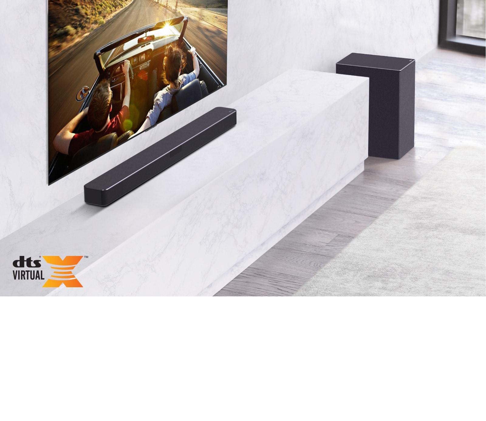 TV treo ở trên tường, loa thanh LG phía dưới, đặt trên kệ đá cẩm thạch trắng, có loa trầm ở bên phải. TV hiển thị một đôi nam nữ trong xe hơi.