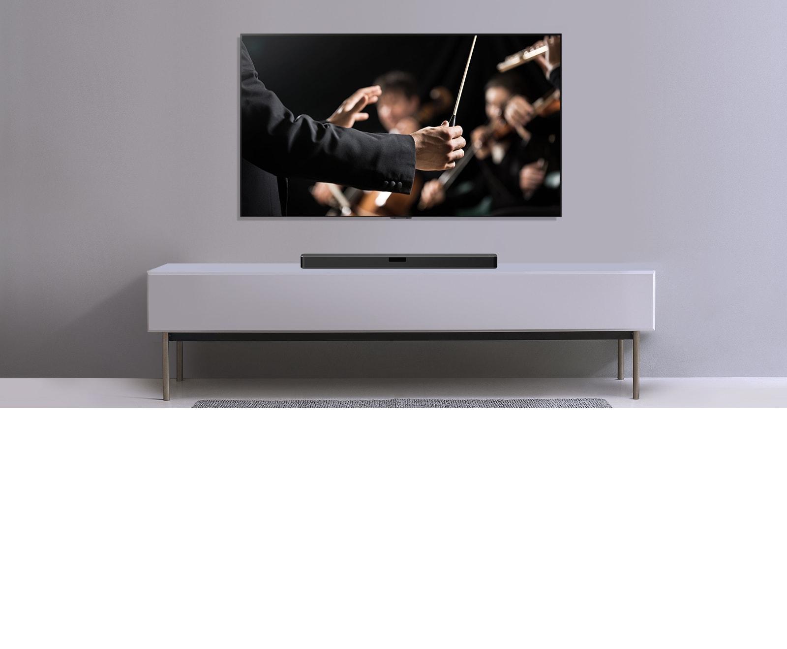 TV được hiển thị trên một bức tường màu xám và Loa thanh LG đặt bên dưới trên kệ màu xám. TV hiển thị một nhạc trưởng đang điều khiển dàn nhạc.