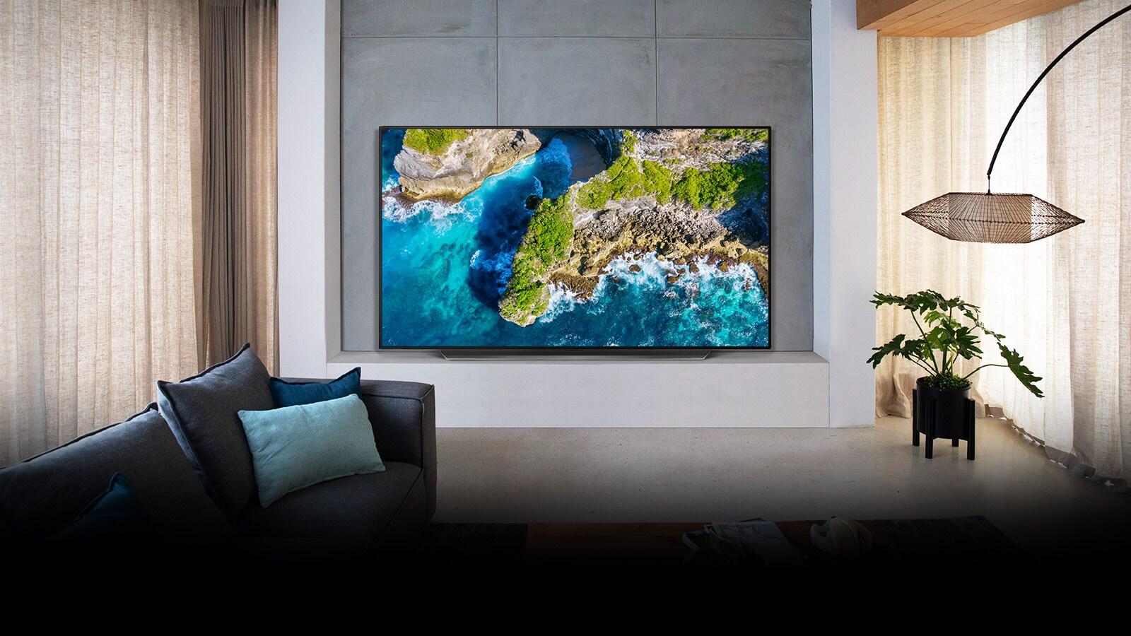 TV hiển thị hình ảnh thiên nhiên trên không trong khung cảnh ngôi nhà sang trọng
