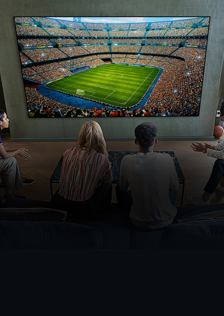 People watching a soccer game on a large TV screen in the living room